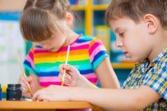 Cute children painting at kindergarten Stock Images