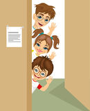 Cute children peeking of the door waving Royalty Free Stock Photos