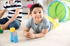 Cute children playing with building blocks on floor, indoors. Cute little children playing with building blocks on floor, indoors royalty free stock image