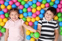 Cute children playing with colorful balls on floor, top view stock image