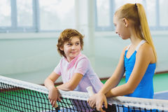 Cute children playing tennis and posing or resting in court indoor Stock Photo