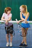 Cute children playing tennis and posing or resting in court indoor Royalty Free Stock Photography