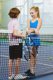 Cute children playing tennis and posing or resting in court indoor Royalty Free Stock Photo