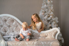 Cute children playing together near Christmas tree indoors. Royalty Free Stock Photos
