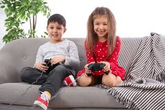 Cute children playing video game on sofa stock photos