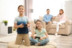 Cute children playing video games while parents resting stock photography