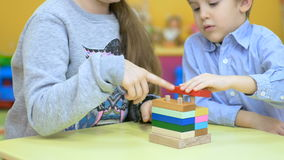 Cute children playing with wooden toys on the table stock video
