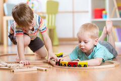 Cute children playing with wooden train. Toddler kids play with blocks and trains. Boys building toy railroad at home or stock photos