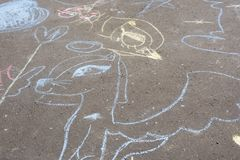 Children`s chalk drawings on ground. Cute children`s chalk drawings on park pavement royalty free stock photos