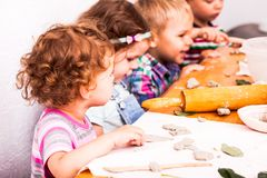 Happy children are engaged with modeling clay royalty free stock photography