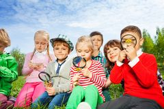 Cute children sit in the meadow with magnifiers Royalty Free Stock Photos