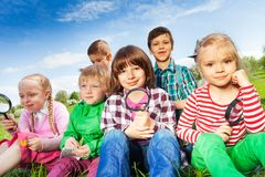 Cute children sitting on grass with magnifier Royalty Free Stock Photos