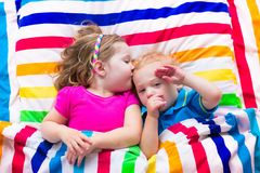 Cute children sleeping under colorful blanket Stock Photo