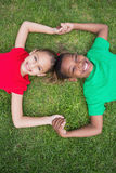 Cute children smiling at camera outside on the grass Royalty Free Stock Images
