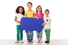 Cute children with speech bubble. Full length portrait of cute little kids in casual clothes holding blue speech bubble, looking at camera and smiling, isolated Royalty Free Stock Photography