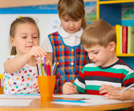 Cute children study at daycare. Cute little children drawing and studying at daycare stock image