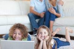 Cute children using a laptop while their parents are watching. In their living room Stock Images