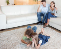 Cute children using a tablet computer while their parents are wa. Tching in their living room royalty free stock photo