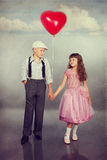 Cute children walking with a red balloon Stock Photos