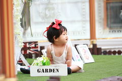Cute Chinese baby girl play flowers in a garden Royalty Free Stock Photo