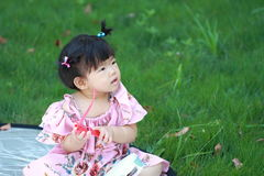 Cute Chinese baby girl play glasses on the lawn Royalty Free Stock Photography
