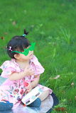 Cute Chinese baby girl play glasses on the lawn Stock Photography