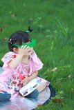 Cute Chinese baby girl play glasses on the lawn Royalty Free Stock Image