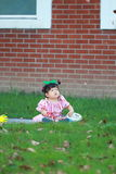 Cute Chinese baby girl play glasses on the lawn Stock Image