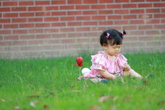 Cute Chinese baby girl play on the lawn Royalty Free Stock Images