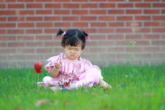Cute Chinese baby girl play on the lawn Royalty Free Stock Photos