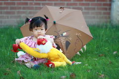 Cute Chinese baby girl play plush toy on the lawn Royalty Free Stock Photos