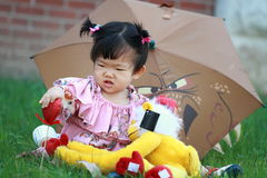 Cute Chinese baby girl play plush toy on the lawn Stock Images