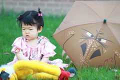 Cute Chinese baby girl play plush toy on the lawn Stock Photo