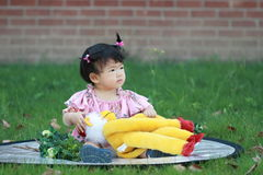 Cute Chinese baby girl play plush toy on the lawn Stock Photos