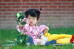 Cute Chinese baby girl play plush toy on the lawn Royalty Free Stock Image