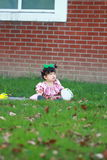 Cute Chinese baby girl wears glasses on the lawn Stock Photography