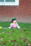 Cute Chinese baby girl wears glasses on the lawn Royalty Free Stock Images