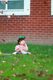 Cute Chinese baby girl wears glasses on the lawn Royalty Free Stock Photo