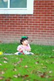 Cute Chinese baby girl wears glasses on the lawn Royalty Free Stock Photos