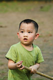 Cute Chinese boy. Cute preschool Chinese boy in green top with piece of wood playing outdoors Royalty Free Stock Photo