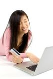 Cute Chinese girl searching to buy online with credit card Royalty Free Stock Image