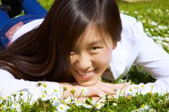 Happy asian woman lying in grass smiling in park in spring Royalty Free Stock Photography