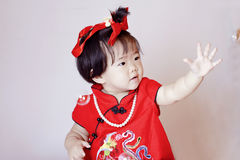 Cute Chinese little baby in red cheongsam play soap bubbles Stock Photography
