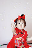 Cute Chinese little baby in red cheongsam play soap bubbles Royalty Free Stock Photo