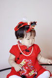 Cute Chinese little baby in red cheongsam play soap bubbles Royalty Free Stock Photos