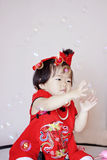 Cute Chinese little baby in red cheongsam play soap bubbles Stock Photos