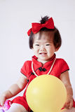 Cute Chinese little baby in red cheongsam play yellow balloon Stock Photography