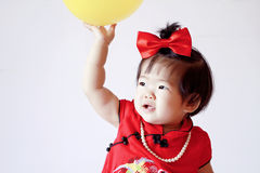 Cute Chinese little baby in red cheongsam play yellow balloon Stock Images