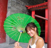 Cute chinese whitwoman smiling with green umbrella Royalty Free Stock Photography