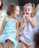 Cute chlidren eating sweet doughnuts Stock Image